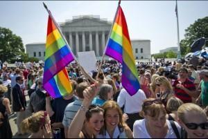 People celebrate the overturning of DOMA and California Prop 8, at the US Supreme Court, by waving rainbow flags.